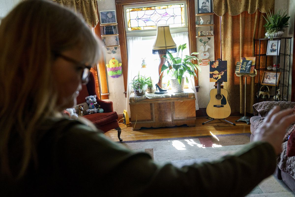 John McCarthy's photo and guitar are displayed as his wife, Christine, stands in their living room on the first Easter without him, Sunday, April 4, 2021, at their home in Lincoln, R.I. John died of complications of COVID-19 on New Year's Day.