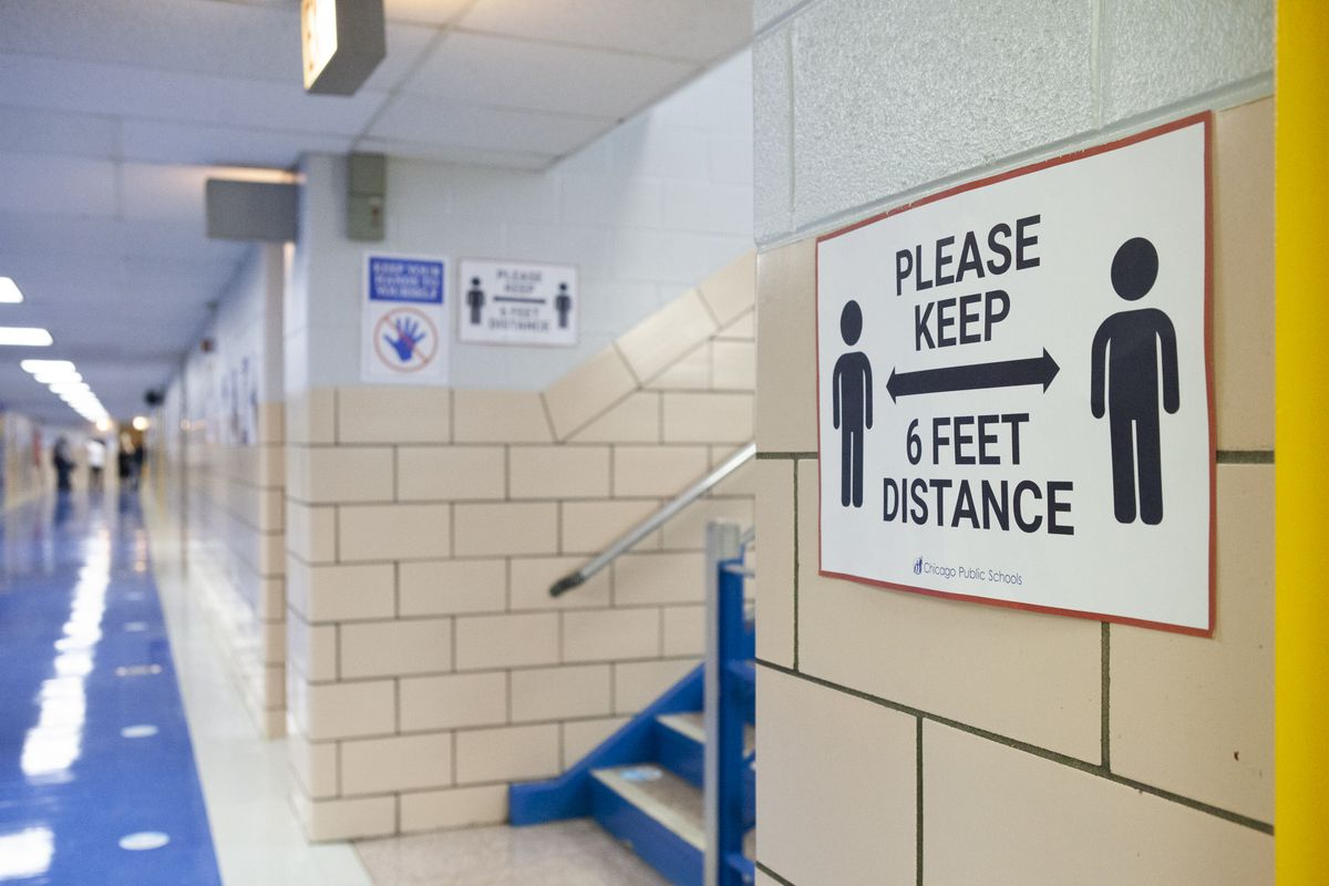 A sign in a school hallway reminding students to keep 6 feet distance apart.