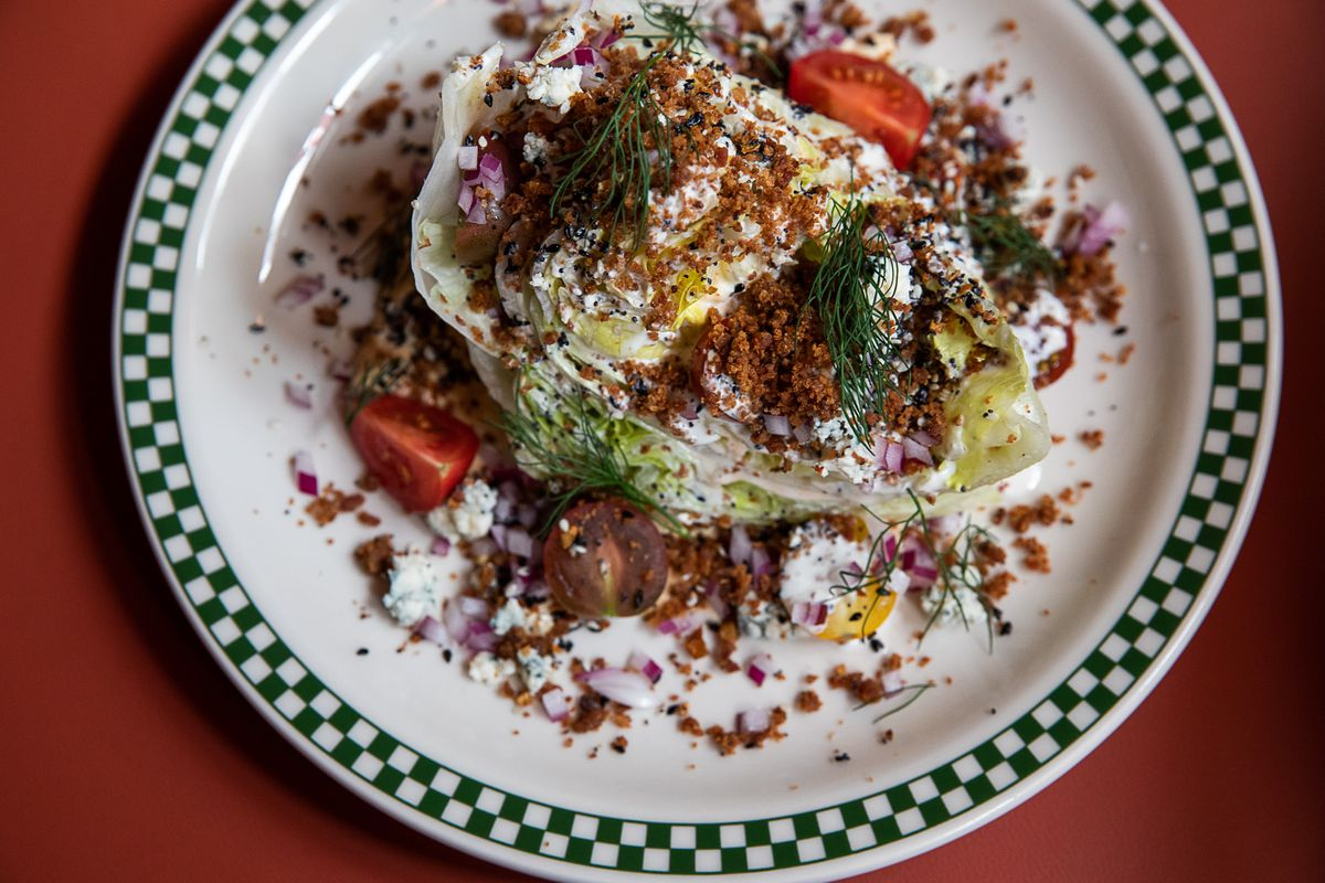 A wedge or iceberg lettuce with sliced cherry tomatoes, creamy blue cheese dressing, crumbles of bacon and bagel spice, and sprigs of dill sits on top of a white plate with green checkerboard edges.
