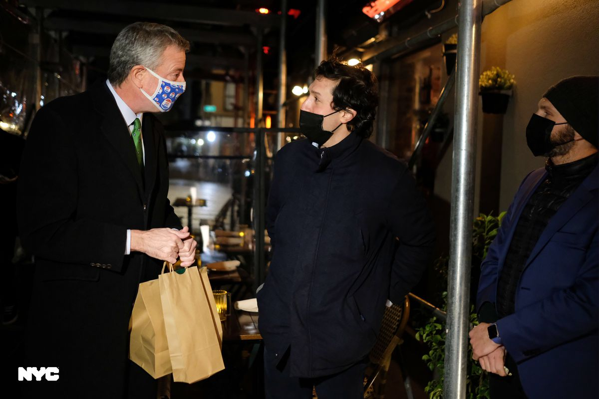 The mayor holds two brown takeout bags while speaking with two restaurant employees in black clothes and black face masks outdoors at Felice 83
