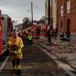 A firefighter arrives on scene where debris fell off a building at 400 South and 500 West in Salt Lake City after a 5.7 magnitude earthquake centered in Magna hit early on Wednesday, March 18, 2020.