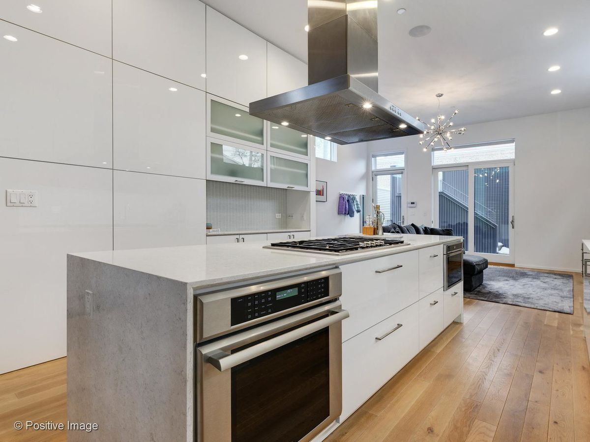The kitchen features shiny white cabinets and a massive island with storage and appliances.