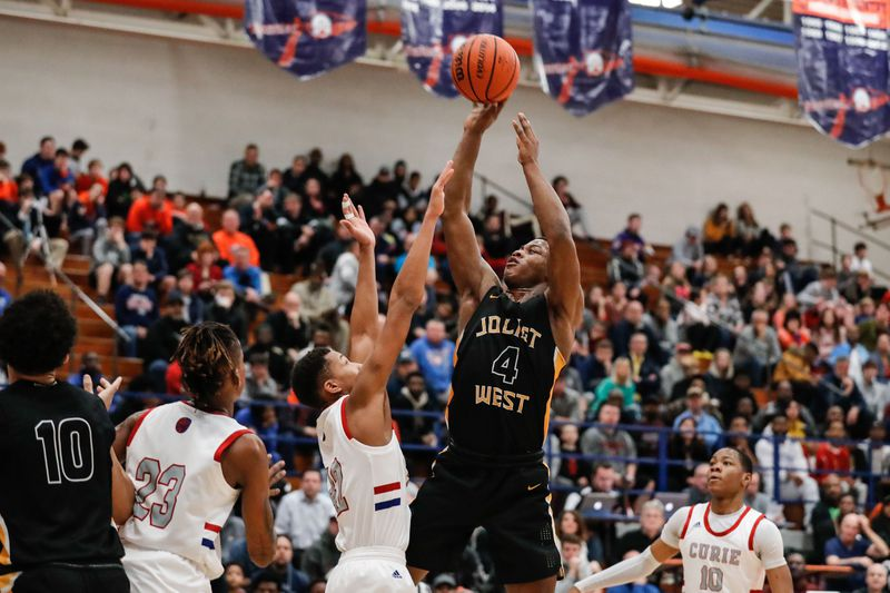 Joliet West's Trent Howland (4) shoots the ball over Curie's defense.