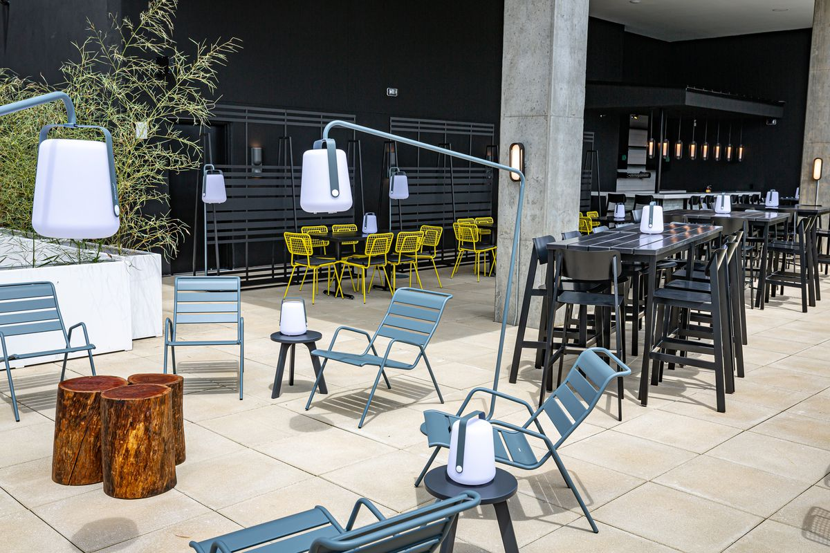 A view of the Cold Beer rooftop patio from the campfire lounge area looking toward the bar and high top table seating