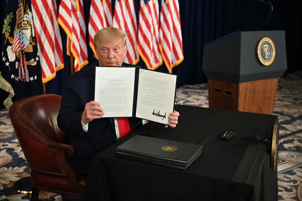 Trump, in a dark suit and bright red tie, is seated and holding a leather folder with an executive order in it near his face. Behind him are a row of US flags, and a podium with the seal of the president of the United States.