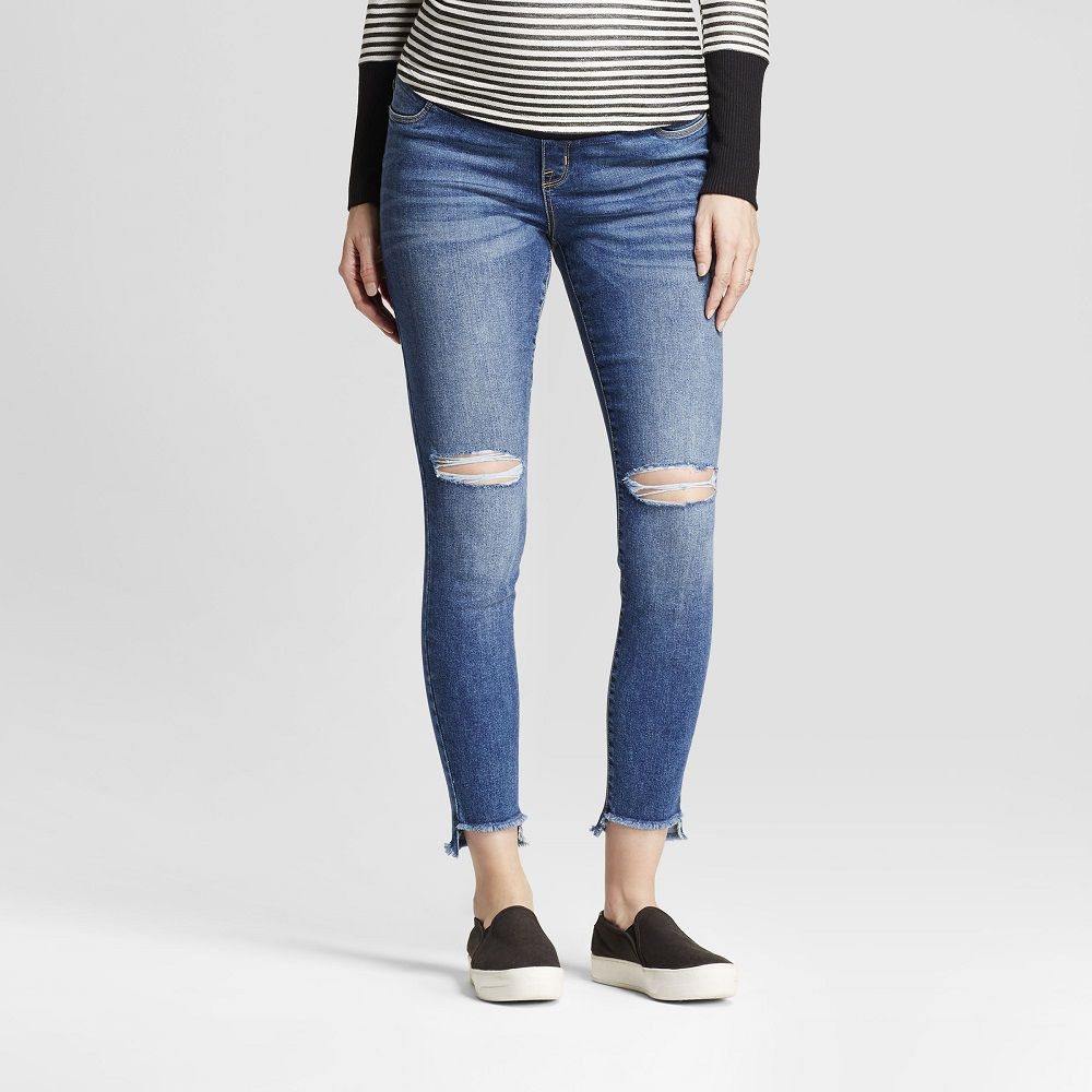 A pregnant woman in ripped jeans