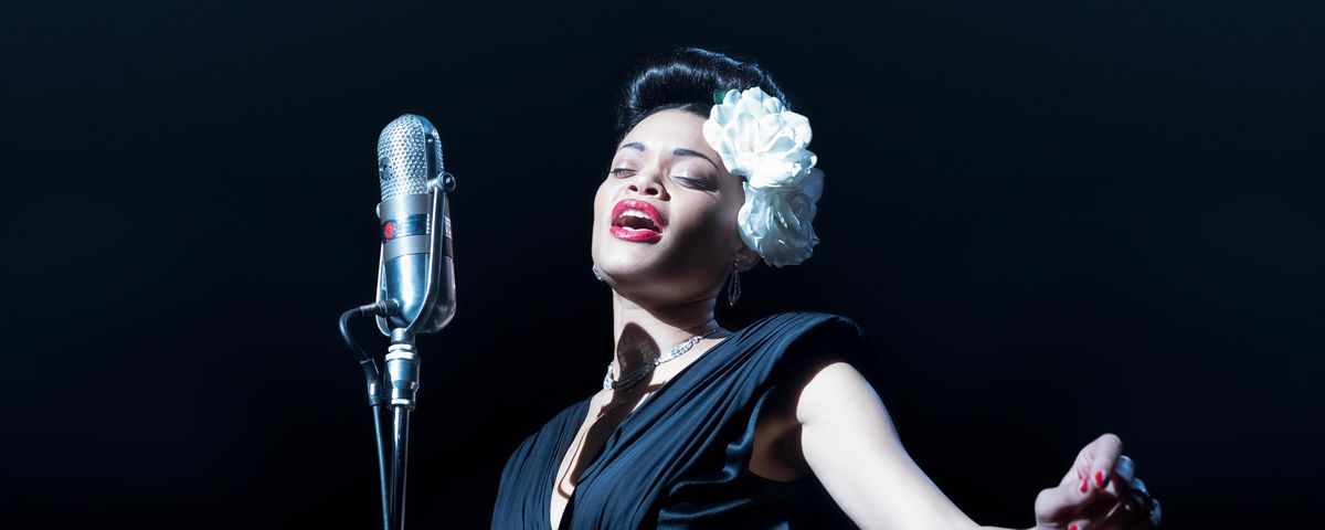 Andra Day sings at a mic in a darkened room as Billie Holiday in The United States vs. Billie Holiday