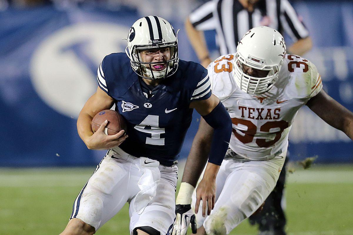 Brigham Young Cougars quarterback Taysom Hill (4) runs away from Texas Longhorns linebacker Steve Edmond (33) BYU and Texas play Saturday, Sept. 7, 2013 at LaVell Edwards stadium. BYU won 40-21.