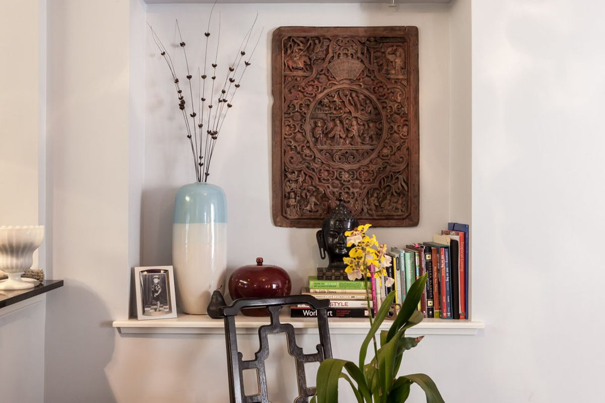 In a nook behind the table hangs a carved wood-panel door from China.