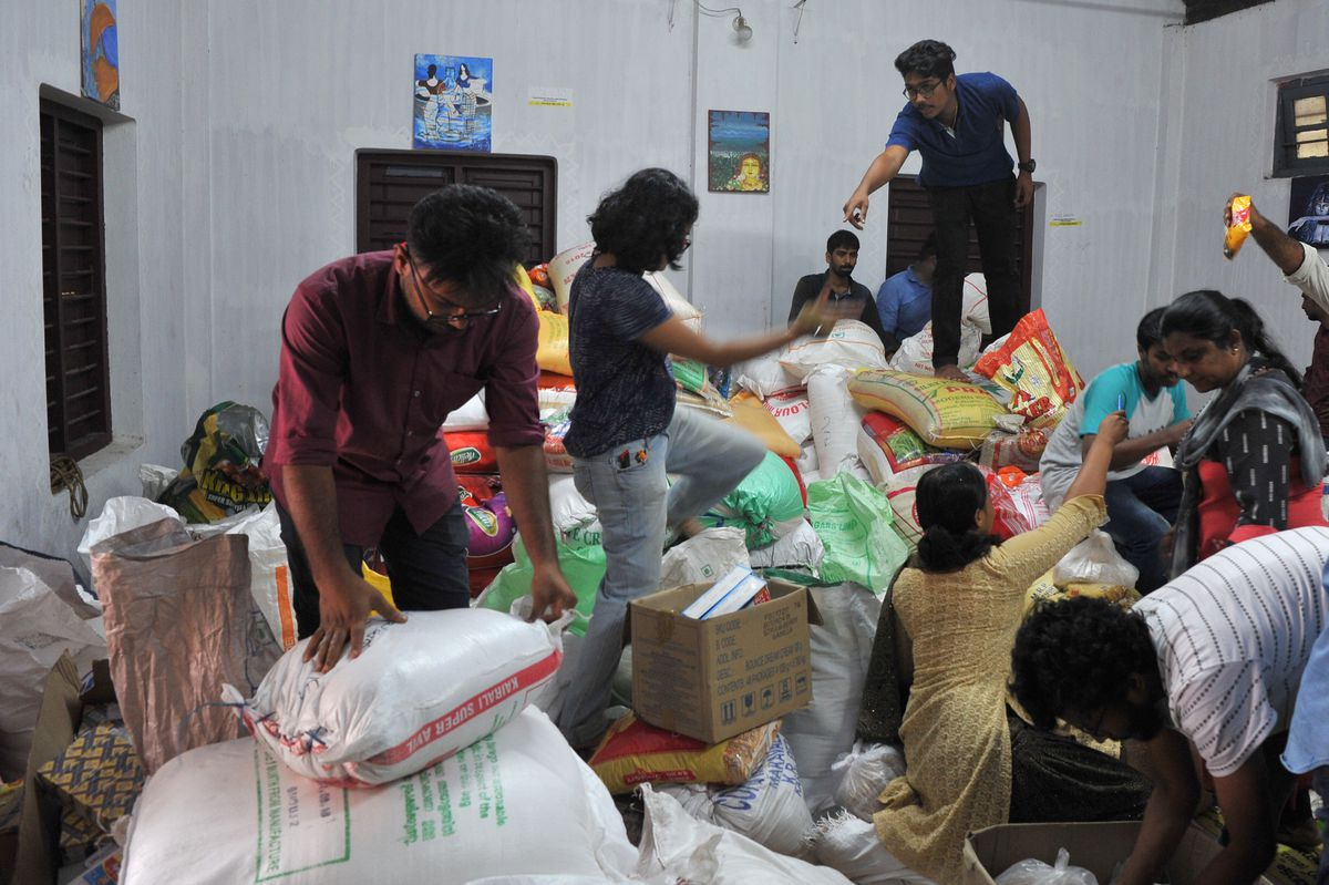 Volunteers help sort flood-relief materials at the District Tourism Promotion Council (DTPC) in Kozhikode district, about 385 km north of Trivandrum, in the south Indian state of Kerala, on August 17, 2018.