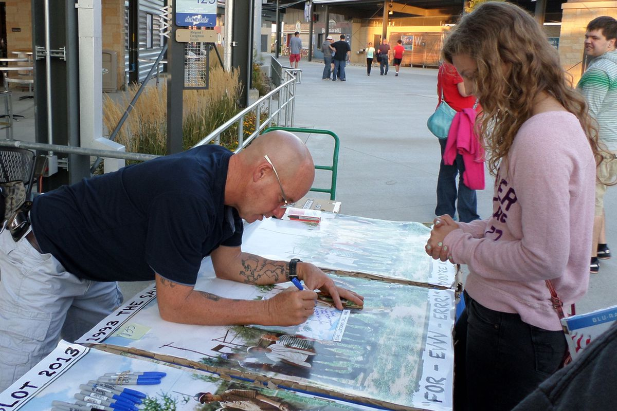 David Mickey Evans signs memorabilia for a fan before a tour stop in Omaha
