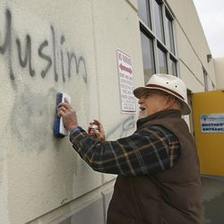 """Tom Garing cleans up racist graffiti painted on the side of a mosque in what officials are calling an apparent hate crime, Wednesday, Feb. 1, 2017, in Roseville, Calif. The Tarbiya Institute was spray-painted with a dozen obscene and racist slurs, including """"Muslim out."""" Garing, a retiree who lives in the area and is not a member of the mosque, volunteered to help clean up."""