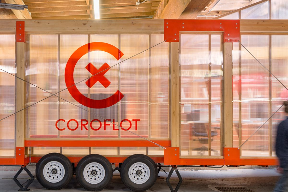 A modular office built with wood and walls made of sheer polycarbonate sits on a trailer inside a warehouse.
