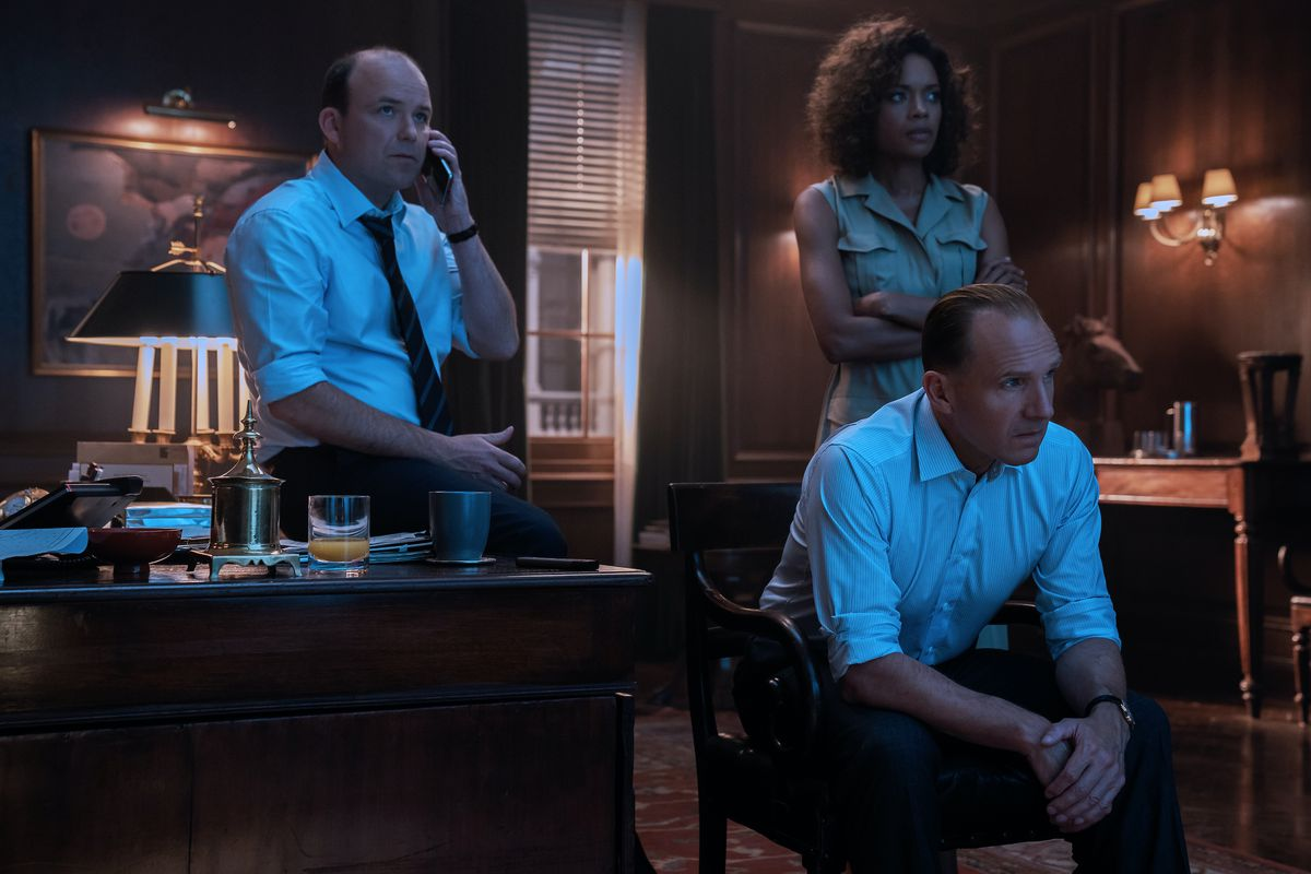 James Bond's enablers, M (Ralph Fiennes) and Moneypenny (Naomie Harris) helplessly hang around the office, waiting to see if he'll come home before curfew in No Time To Die