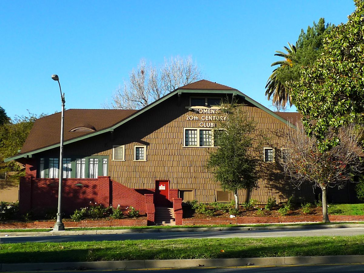 The exterior of the Women's Twentieth Century Club in Los Angeles. The facade is brown with a red staircase in front.