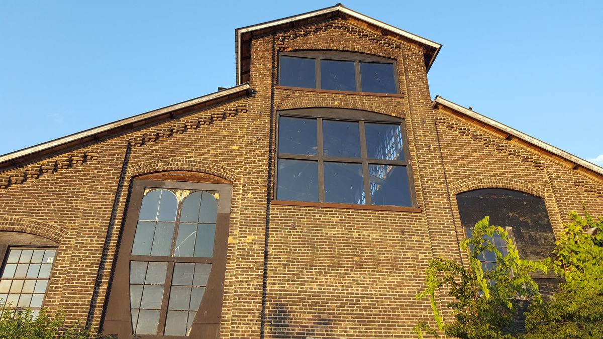A large house with a brown brick facade with multiple windows.