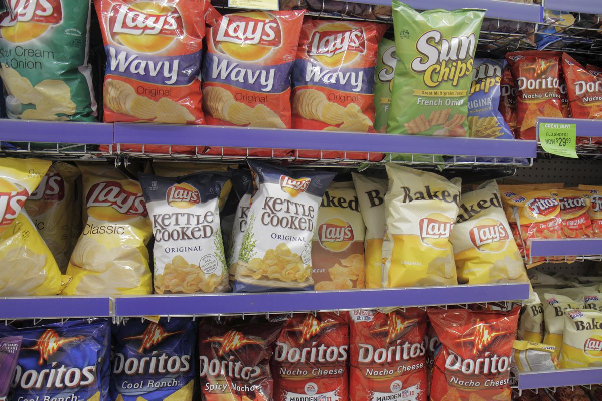 Grocery stores shelves filled with different kinds of chips.