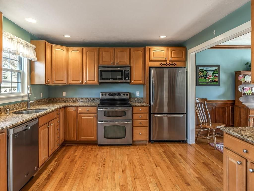 An open kitchen with an L-shaped counter and a double-door fridge.