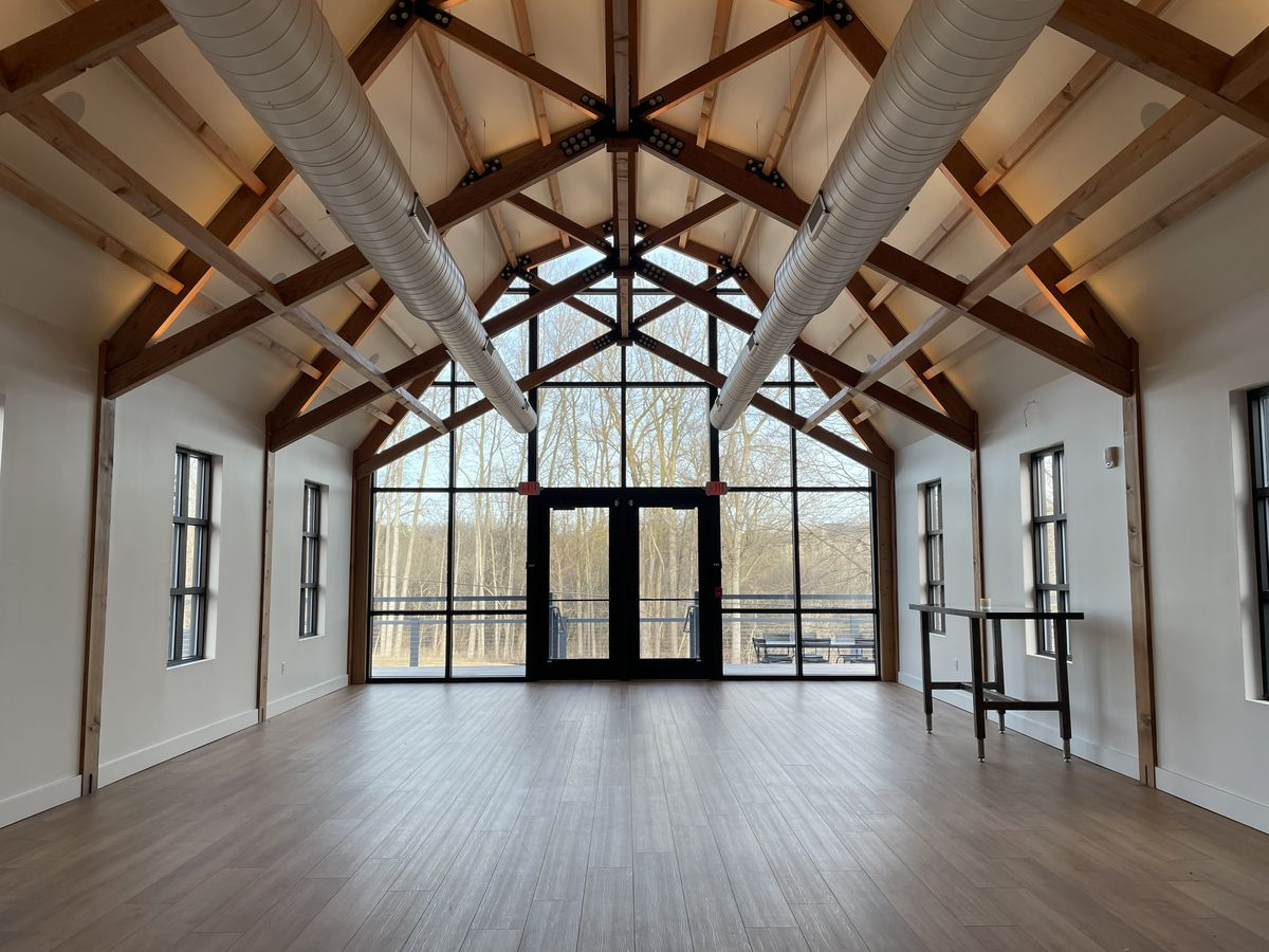 The spacious, two-story room to become the dining room of Dixboro House, once an old barn with wooden beams and floor-to-ceiling windows remains empty while under construction