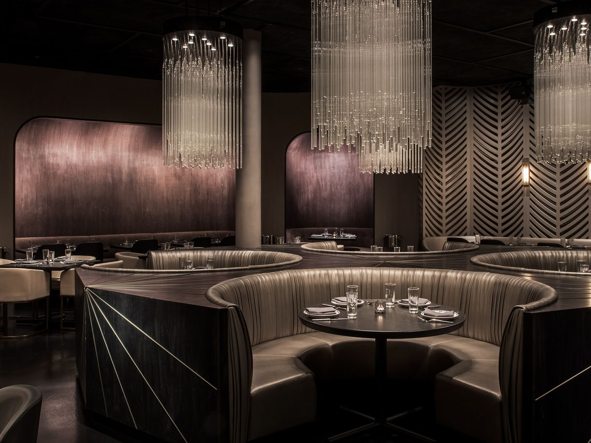 A dark restaurant dining room with many booths.