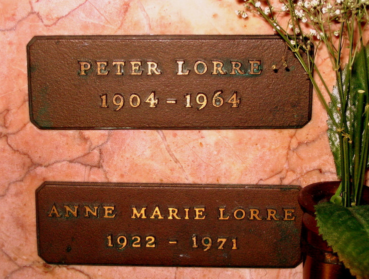 A pink marble gravestone. There are two plaques on the gravestone with words that read Peter Lorre 1904-1964 and Anne Marie Lorre 1922-1971.