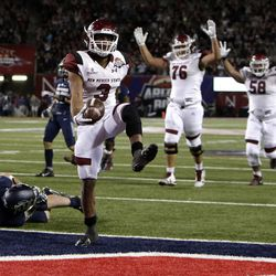 New Mexico State running back Larry Rose III (3) leaps over Utah State linebacker David Woodward to score a touchdown in overtime and defeat Utah State 26-20 in the Arizona Bowl NCAA college football game, Friday, Dec. 29, 2017, in Tucson, Ariz. (AP Photo/Rick Scuteri)