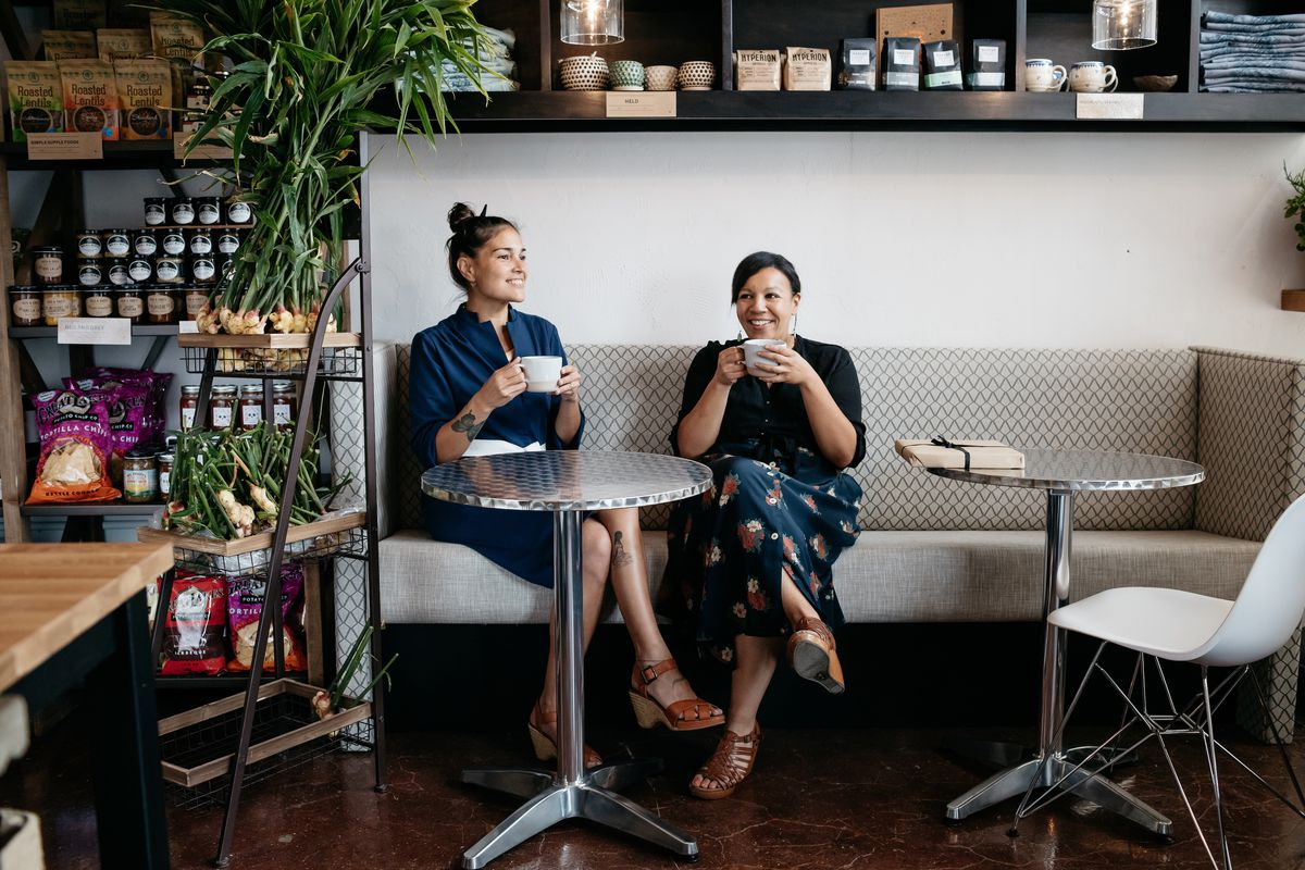 Two women holding coffee mugs sit at a banquette behind a small round table. There are shelves on the left holding bags of chips and jars of snacks and shelves above the two women holding pantry items.