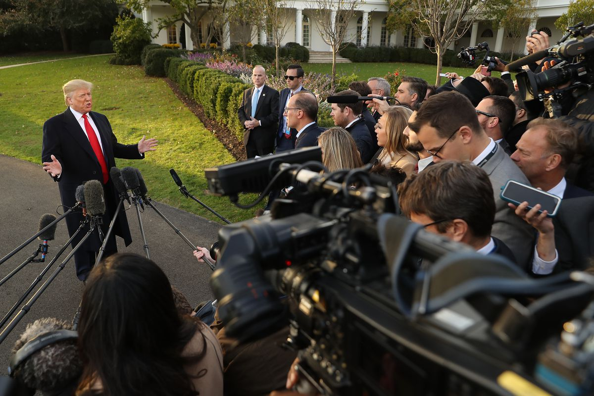 President Donald Trump stands outside the White House and speaks in front of a crowd of reporters.
