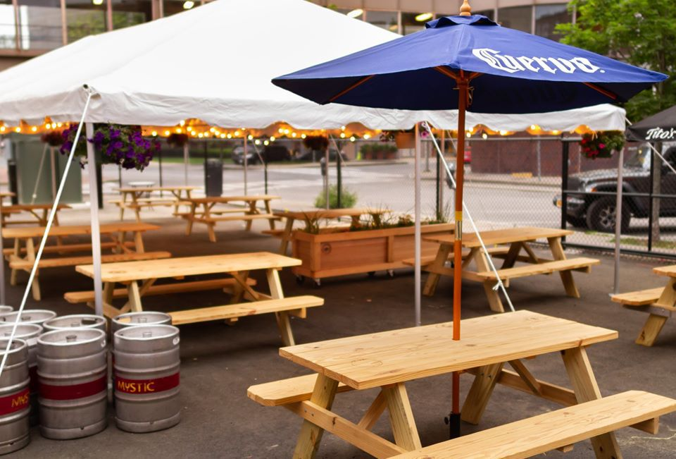 A beer garden with light wooden picnic tables, dark blue umbrellas, and a white tent covering part of the area