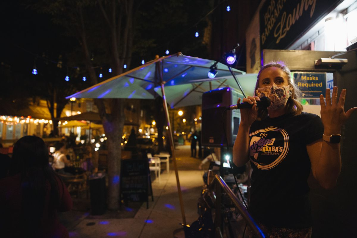 woman outside of bar speaking into microphone with umbrellas and string lights behind her