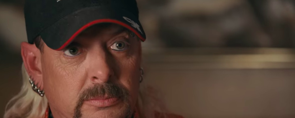 Joe Exotic, a walrus-mustached, mulleted man in a feed cap, looks into the camera in a shot from the first episode of the documentary Tiger King.