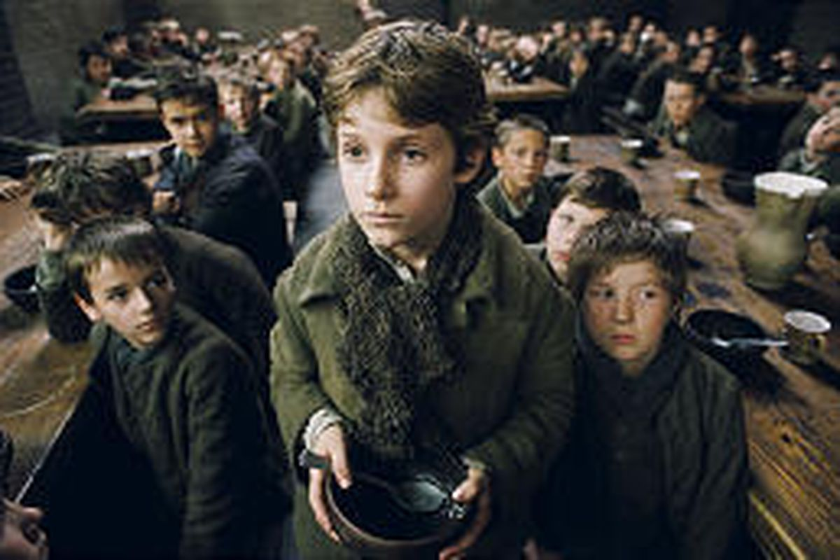 """Oliver Twist, played by Barney Clark, is forced to live in a workhouse lorded over by the awful Mr. Bumble, who cheats the boys of their meager rations in Columbia Pictures' """"Oliver Twist,"""" directed by Roman Polanski."""