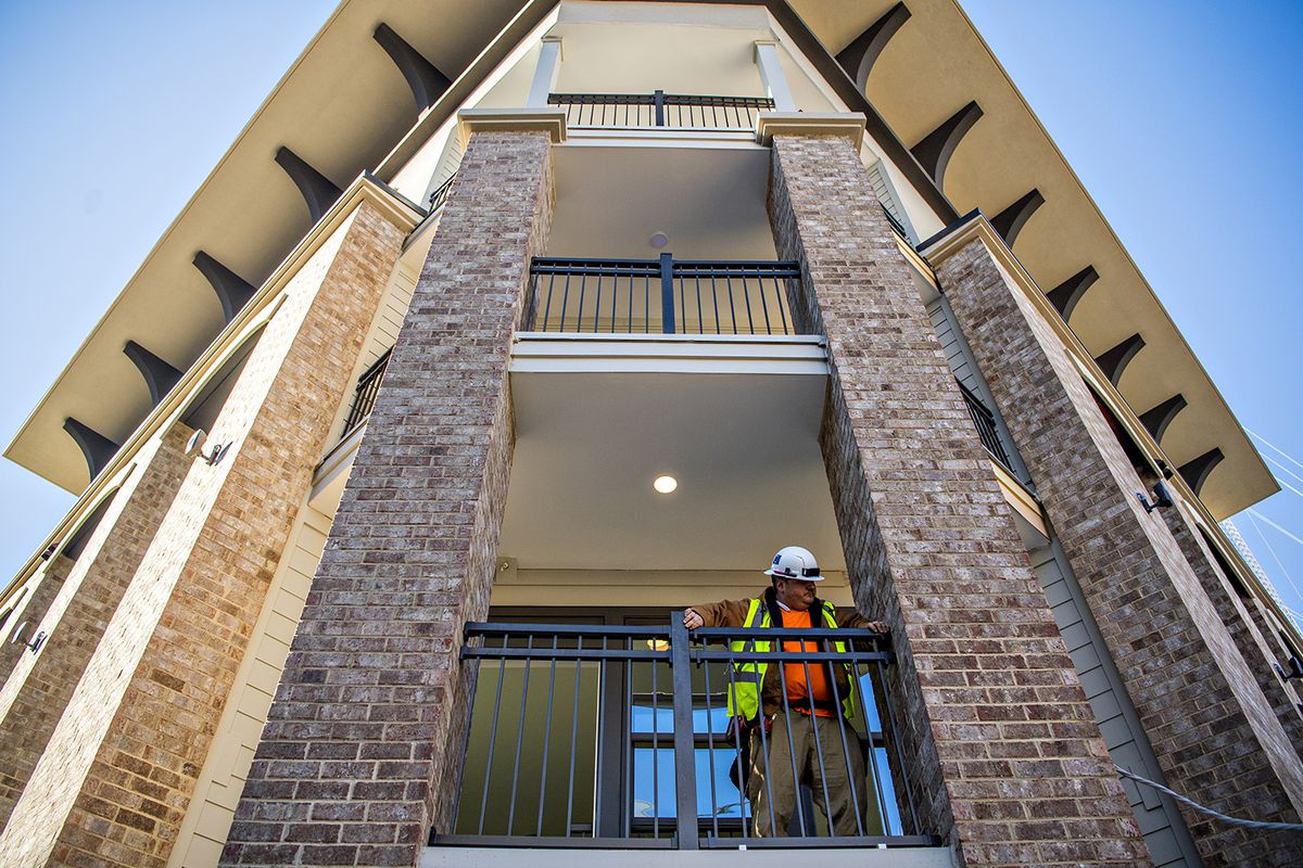 A worker building railing at a new apartment complex beneath a blue sky.