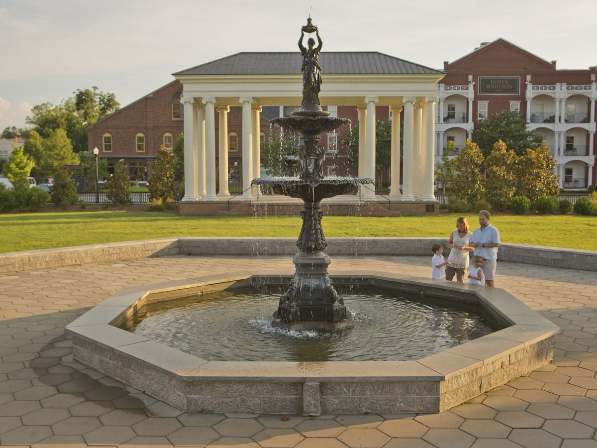In the foreground is a fountain in a courtyard. There is a large building in the distance that has many white columns surrounding its entryway. There are people walking next to the fountain.