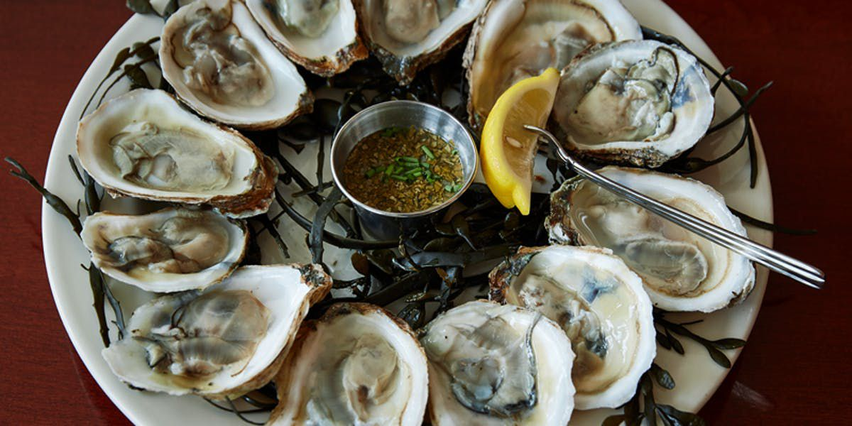 A plate of raw oysters with lemon and sauce at the center.