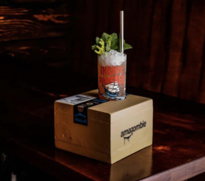 """A pink cocktail with ice and green leafy garnishes sits atop a cardboard box that says """"Amazonmbie"""" in a font that resembles Amazon"""