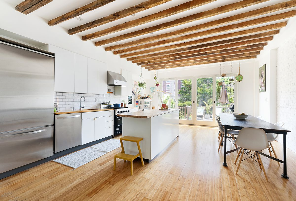 A kitchen with wood beams in its ceilings and white cabinetry.
