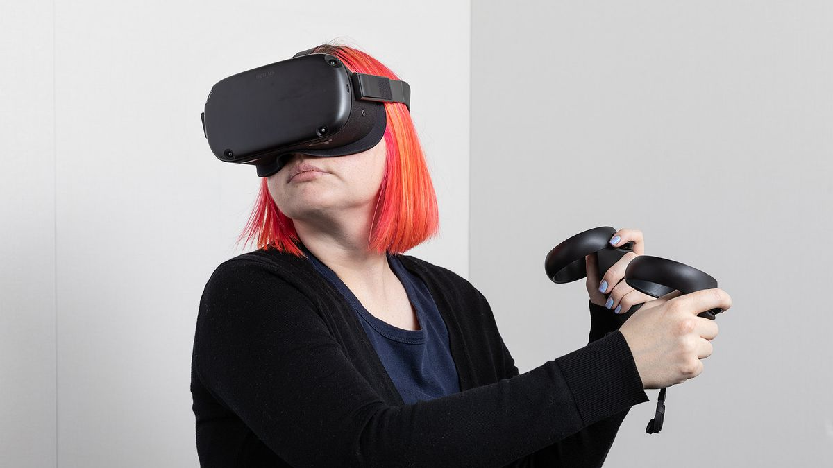 a white woman with orange hair wearing an Oculus Quest headset and looking to the right as she holds two Oculus Touch controllers