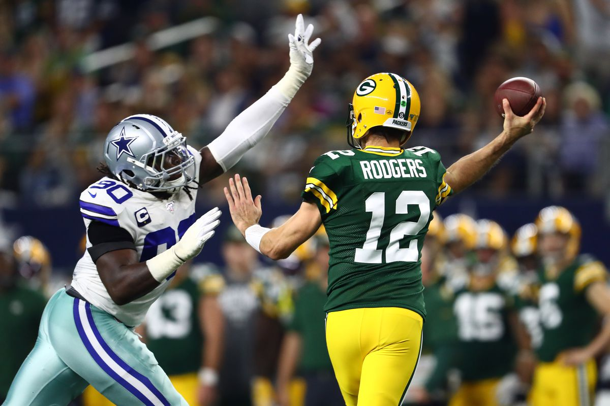 Green Bay Packers quarterback Aaron Rodgers throws under pressure from Dallas Cowboys defensive end DeMarcus Lawrence in the fourth quarter at AT&T Stadium.