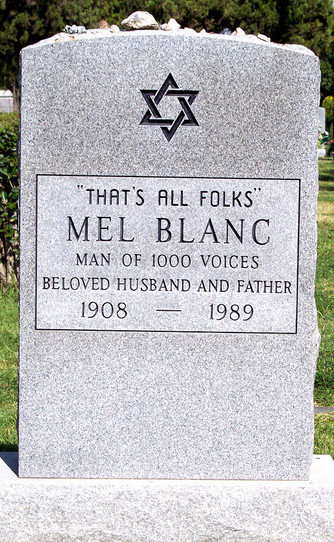 A grey gravestone in the Hollywood Forever cemetery. The words on the gravestone read That's all folks, Mel Blanc, man of 1000 voices beloved husband and father 1908-1989