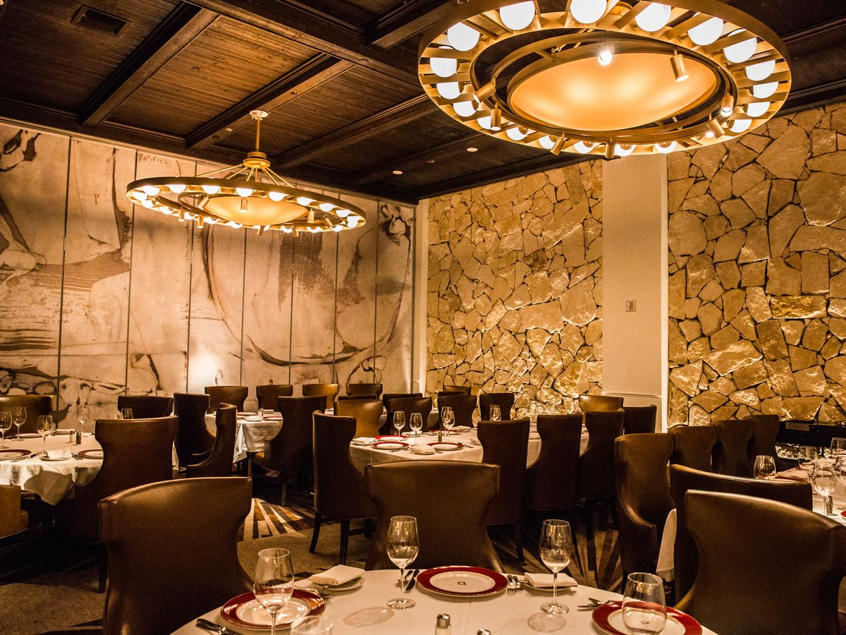 A dramatic restaurant interior with chandeliers and chocolate brown chairs