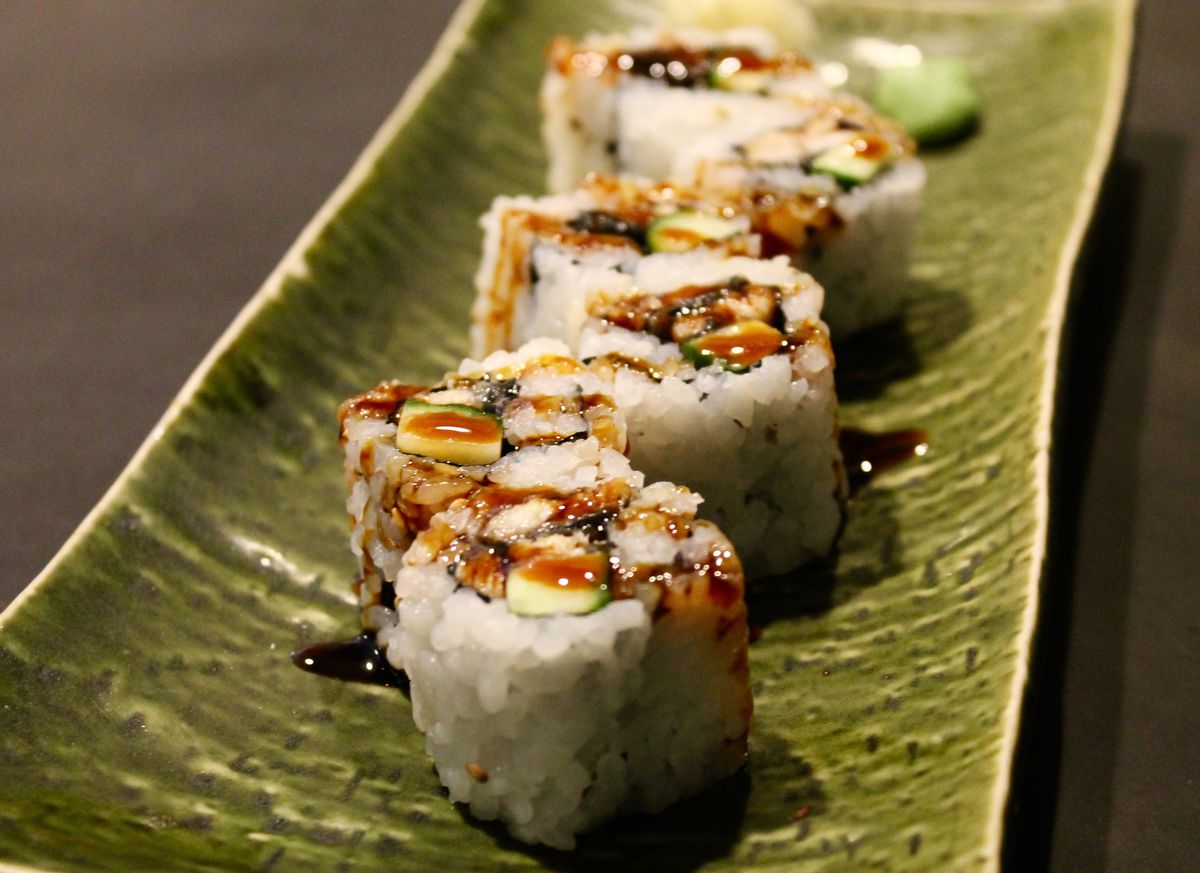 Six pieces of a sushi roll line a green rectangular plate