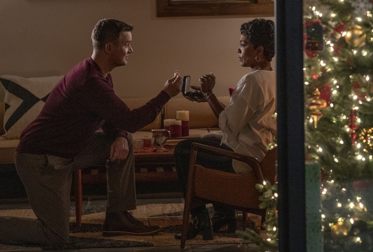 Bobby proposing to Athena with a Christmas tree in the background
