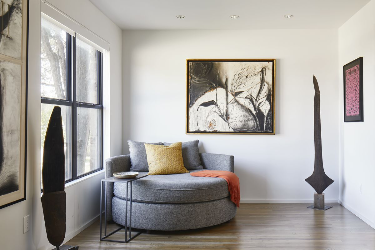 A room with a large circular arm chair that has multiple assorted pillows and an orange throw blanket. Works of art hang on the white walls. There is a window.