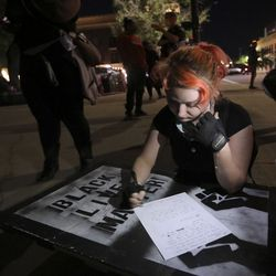 Elly Swedberg files a police report outside of the Provo Police Department after a white SUV drove into protesters and hit her during a rally against police brutality and racism in Provo on Monday, June 29, 2020.