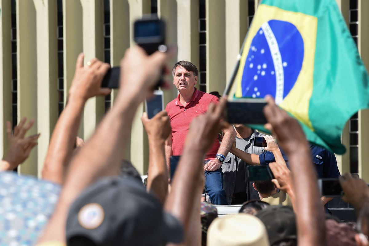 Bolsonaro, in a red polo shirt, speaks amid a dense crowd dressed in green and yellow, as many raise their phones and flags.