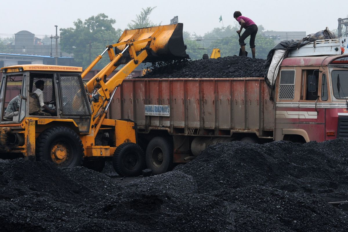 An Indian labourer adjusts coal being loaded onto a truck at the Kankaria Railway Yard in Ahmedabad on September 5, 2012.