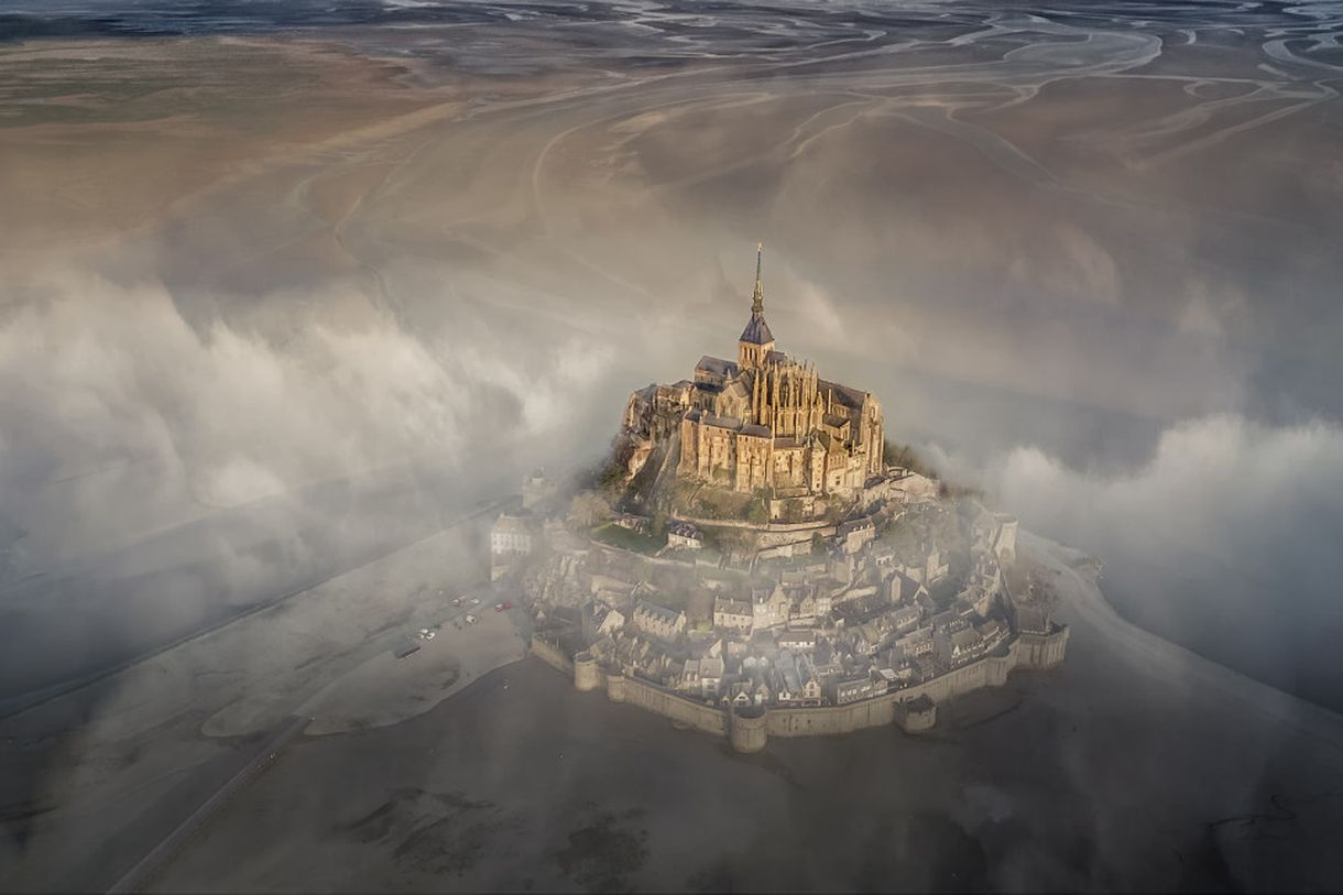 """""""The famous monastery of Mont Saint Michel during a foggy morning."""""""