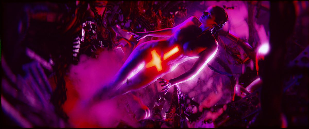 A naked woman, lit in purple, with a glowing red inverted cross covering her stomach and groin, stands in an abstract purple landscape, surrounded by mist and tree-like structures