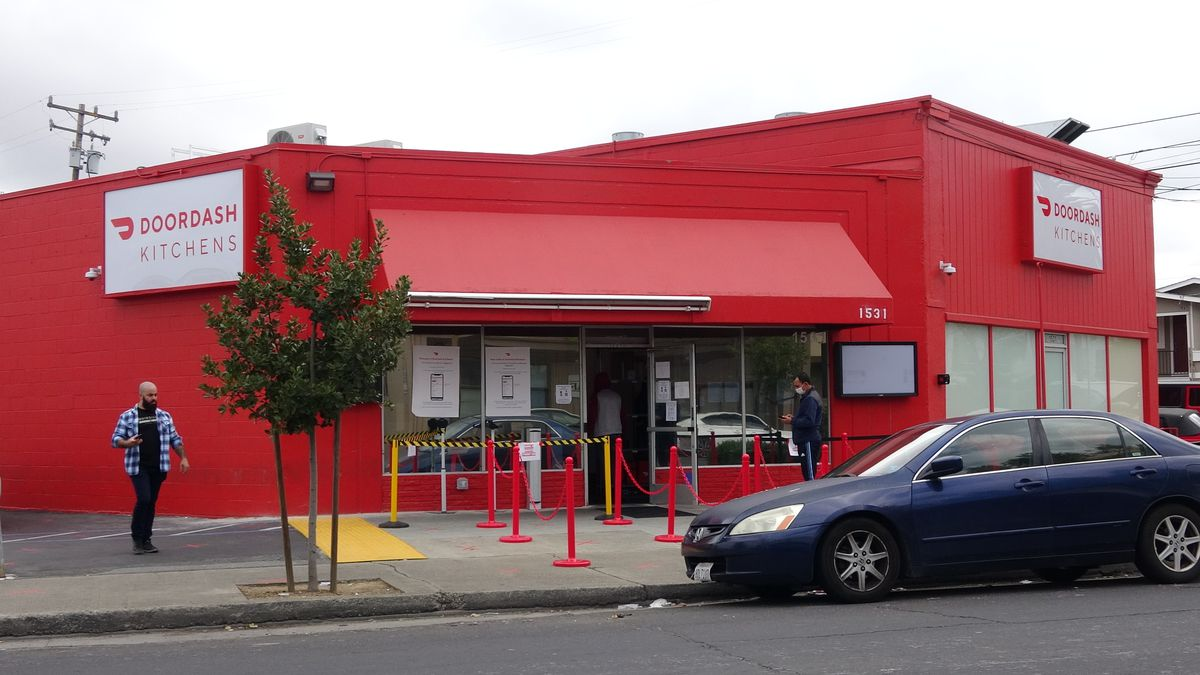 """Red building with """"Doordash Kitchens"""" signage on the side."""
